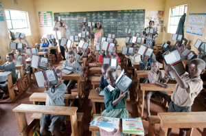 Students in Kenya proudly display their new E-readers provided by Worldreader.org.